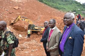 """United Methodist Bishop John Yambasu (center, at right) joins with other clergy from the Council of Churches in Sierra Leone to visit two communities hit by flooding and a mudslide near Freetown, Sierra Leone. """"The amount of homes that were buried in that rubble ... to know that I was really standing on top of human beings crushed by the landslide was most devastating for me,"""" he said."""" Photo by Phileas Jusu, UMNS."""