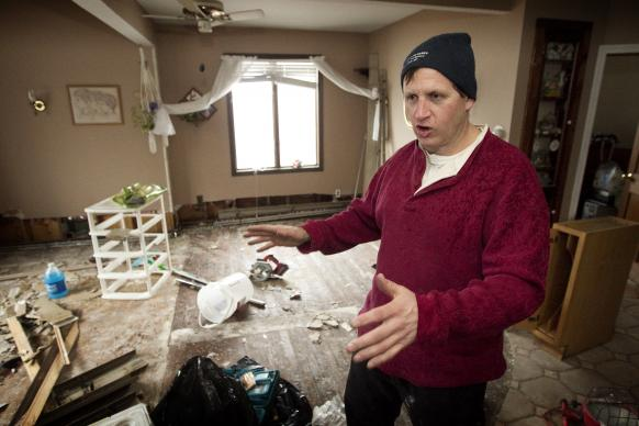 As the storm's first anniversary approached, Peter Vasquenz describes damage to his mother's home in the Staten Island borough of New York following Hurricane Sandy in November 2012. Vasquenz, a firefighter in Brooklyn, had been ripping out waterlogged drywall and flooring. File photo by Mike DuBose, UMNS.
