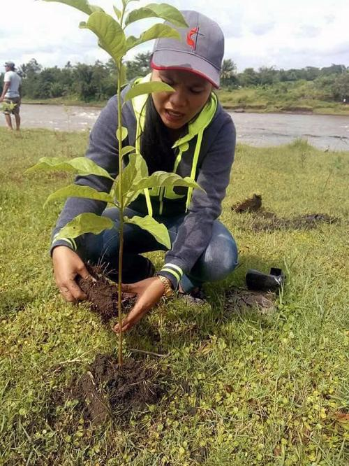 A participant in a tree-planting project in the Davao area of the Philippines kneels to settle a sapling in the soil. Church members and leaders joined in the tree-planting along the Pulangi River. Photo courtesy of the Rev. Rogemer Sison.