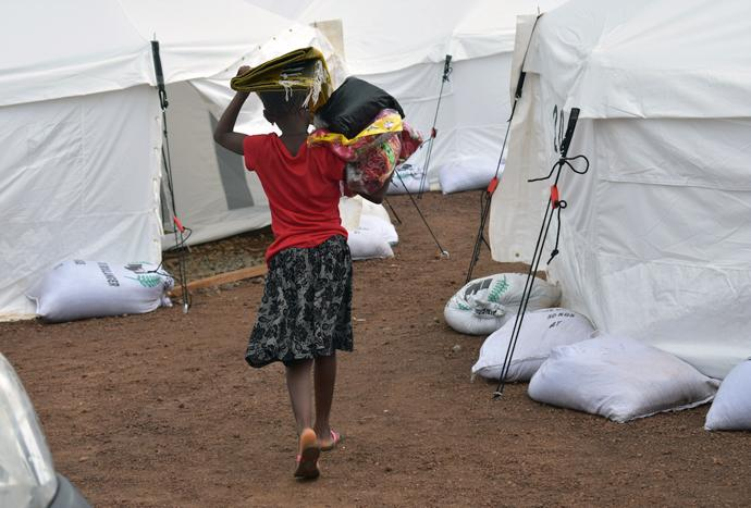 A disaster-displaced girl returns to her tent after collecting relief items distributed by the Council of Churches in Sierra Leone at a new relocation camp in Juba. Photo by Phileas Jusu, UMNS.