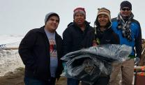 Dallas Parker, left, the Rev. David Wilson and Tim Byington, right, present thermal coats to a camp volunteer at the Oceti Sakawin Camp at Standing Rock. The coats were donated by the Urban Inter-Tribal Center of Texas. Photo courtesy of Dallas Parker.