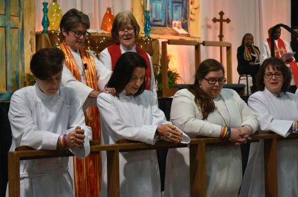 "The Rev. M Barclay, at left, kneels at the Northern Illinois Conference's commissioning of provisional deacons on June 4 in St. Charles, Ill. Barclay is the first openly ""non-binary trans person"" to become a United Methodist deacon. Photo by Anne Marie Gerhardt, Northern Illinois Conference."