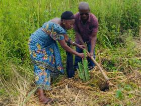 A man and woman work together to plant a sapling as part of reforestation efforts by the church in East Congo. Photo by Judith Yanga, UMNS.