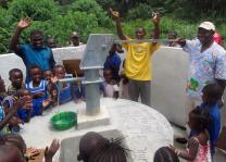 Children and families clap in celebration as Bishop John K. Yambasu (far right in light blue shirt) pumps the first water from a new well during a dedication ceremony in Manjama in the Bo District of Sierra Leone. A Global Health agency initiative provided each community a four-seat toilet and a hand-dug well for United Methodist primary schools in Manjama and Fulawahun. Photo by Phileas Jusu, UMNS.
