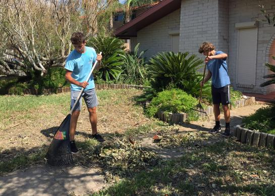 Two teens from First United Methodist Church in Corpus Christi, Texas, rake and remove debris after Hurricane Harvey devastated areas of Texas with winds and flooding. Youth from the church conducted clean ups in both Corpus Christi and Portland. Photo courtesy of Whitney Hendley.