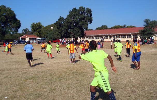 Opposing teams rush for the ball in the final soccer match between the Domboramwari Circuit team and the Harare West District Team at Selborne Routledge Primary School in Harare, Zimababwe. The match was part of a sports event sponsored by Zimbabwe Episcopal Area women's organization, RukwadzanoRweWadzimai. Photo by Kudzai Chingwe, UMNS.