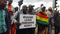 "Crowds in Harare, Zimbabwe, carried signs and chanted ""Mugabe must go"" after the military there placed President Robert Mugabe under house arrest."
