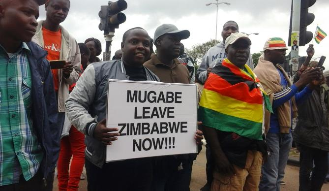 """Crowds in Harare, Zimbabwe, carried signs and chanted """"Mugabe must go"""" after the military there placed President Robert Mugabe under house arrest."""