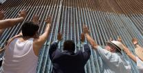 Parishioners of the Border Church in Tijuana, Mexico, raise their arms skyward beneath the border fence at El Faro Park in Tijuana. The Methodist Church of Mexico and The United Methodist Church in the U.S. share communion each Sunday across the border. Photo by Mike DuBose, UMNS.