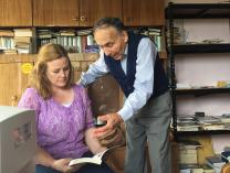The Rev. Bodijar Popov shows the Rev. Jessica Morris-Ivanova one of his father's books. Father and son, Simeon and Bodijar Popov, both served Shumen Methodist Church in Bulgaria. Photo by Ginny Whitehouse.