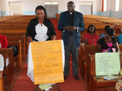 Kuda Dozva (holding sign) talks about fundraising and pastoral care during training held in Harare, Zimbabwe, for church leaders from the South Congo Conference. Photo by Chenayi Kumuterera, UMNS.
