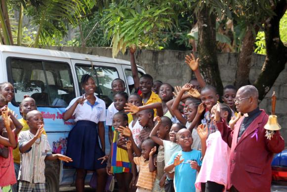 The Rev. Robert N. Sieh, director of The United Methodist Church's Bishop Judith Craig Children's Village, and children pose with their new bus.  Photo by E Julu Swen, UMNS.