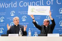 The Rev. Olav Fykse Tveit, the World Council of Churches' top executive, left, and Andrzej Choromański of the Roman Catholic Church's Pontifical Council for Promoting Christian Unity, present a graphic symbol of the June 21 visit by Pope Francis to the WCC during a May 15 press conference in Geneva. Photo by Albin Hillert/WCC