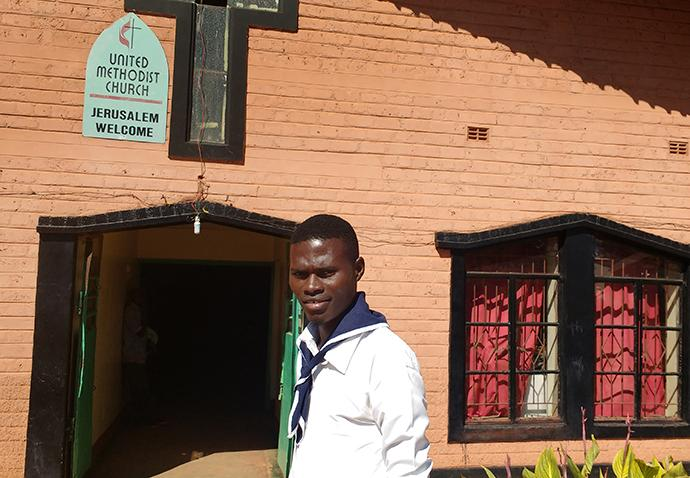 Misheck Mukumbi, a young adult at Jerusalem United Methodist Church, indicates the new water tank. He said having clean water by the church will help both the parish and community combat cholera. Photo by John Chikuta, UMNS.