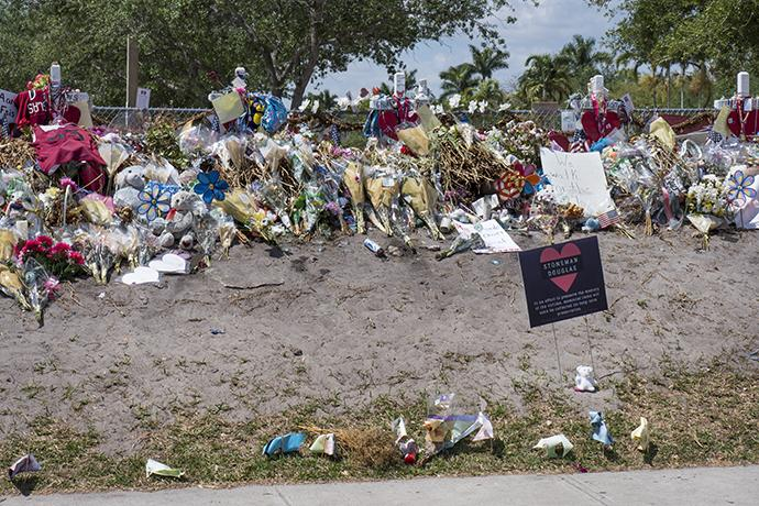 People continue to bring flowers and tributes to place outside Marjory Stoneman Douglas High School where 17 people were killed on Feb. 14. Photo by Kathy L. Gilbert, UMNS.