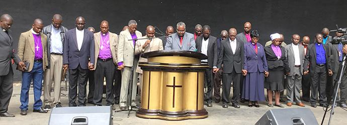 Heads of church denominations join hands in unity as they pray for upcoming elections. Photo by Chenayi Kumuterera, UMNS.