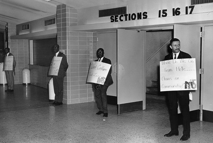 """Where do we go from here… Chaos or Community?"" appears on the sign held by the Rev. Gilbert H. Caldwell by the entrance to the plenary for the 1968 Uniting Conference in Dallas. The phrase is the title of the Rev. Martin Luther King Jr.'s final book, and a reminder of the church's ongoing call to confront racism. Photo courtesy of the Archives and History."