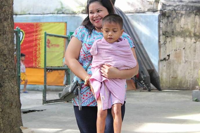 A volunteer carries a child after his bath at Central United Methodist Church in Manila, Philippines. During the church's Ligo Land ministry, volunteers help bathe about 40 children each week. The kids get new clothes and enjoy snacks and stories in the church. Photo courtesy of Aquilino Javier.