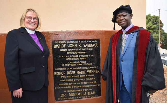 Bishop John Yambasu (right) poses with German Bishop Rosemarie Wenner by a plaque that names the school of theology at United Methodist University after Wenner. The dedication ceremony was held Jan. 27 in Freetown, Sierra Leone. Photo by Phileas Jusu, UMNS.