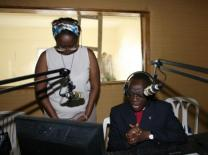 Lydie Acquah and Bishop Benjamin Boni pray in the studio of the new United Methodist radio station in Abidjan, Côte d'Ivoire. Photo by Ginny Underwood, UMNS.