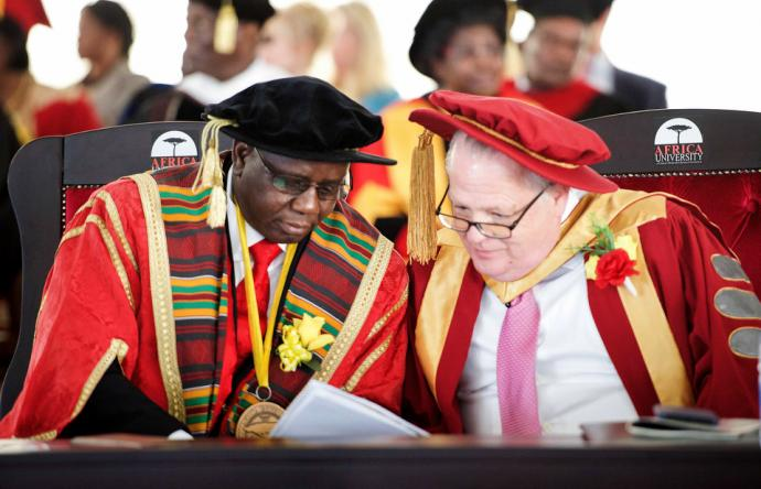 Munashe Furusa (left), vice chancellor of Africa University, confers with Timothy Keating during graduation. Keating, an executive with the Boeing Co., was guest of honor at the ceremony. His family has endowed a permanent scholarship valued at $130,000 for female students studying education. Photo by the Africa University Department of Information and Public Affairs.