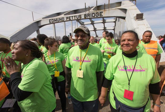 United Methodist Bishop Woodie W. White (center) crosses the Edmund Pettus Bridge in Selma, Ala., during the 50th anniversary observance of the