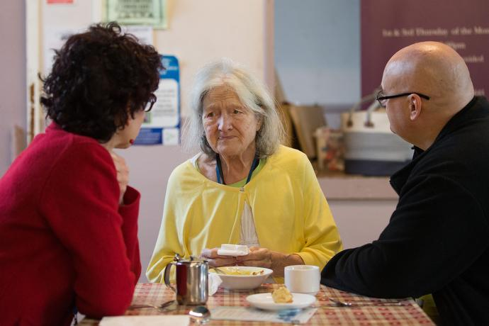 Patricia (center) visits with the Rev. Kathleen LaCamera Loughlin (left) and Andy Hodgkins during the community café. Loughlin is a United Methodist chaplain working in the area and Hodgkins is chair of the community garden and workshop at the center. Photo by Mike DuBose, UMNS.