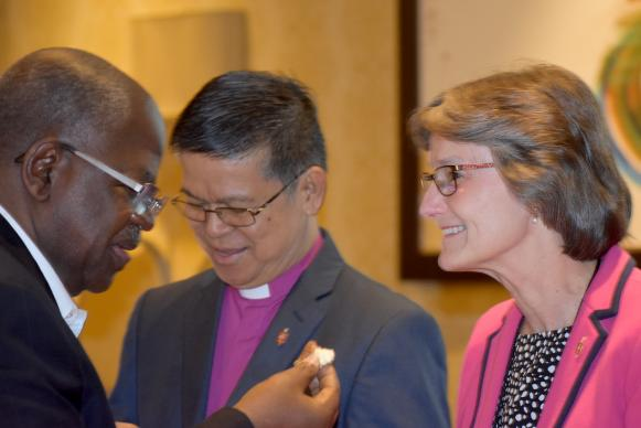 From left, Bishop David Yemba takes communion from Bishops Ciriaco Q. Francisco and Sandra Steiner Ball on May 3 during the meeting of the Council of Bishops in Chicago. Photo by Heather Hahn, UMNS.