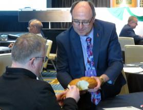Michigan Area Bishop David Bard serves communion bread to Nordic-Baltic Area Bishop Christian Alsted during closing worship at the meeting of the Council of Bishops. Photo by Sam Hodges, UMNS.
