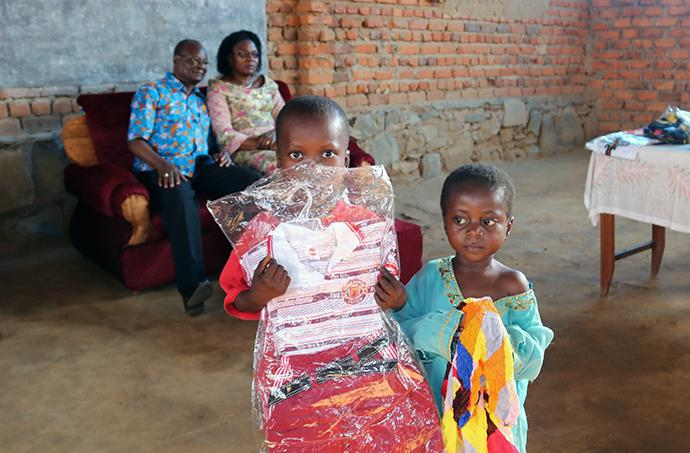 Two orphans who were brought from the Kasongo-Samba District of the Democratic Republic of Congo to Kindu hold up clothing they received. In addition to providing supplies for those displaced by rebel violence, the church team also helped relocate some widows and orphans. East Congo Area Bishop Gabriel Yemba Unda, along with his wife, Marie Claire Unda, are seated in the background. Photo by Judith Osongo Yanga, UMNS.