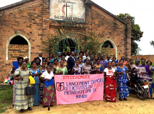 A group poses for a photo with Bishop Gabriel Yemba Unda (center, left behind banner) outside Kitumaini United Methodist Church during training provided for the wives of future pastors who are attending Kindu United Methodist University in the Democratic Republic of Congo. The East Congo Episcopal Area organizes the faculty of theology and provides classes in several trades, languages, culinary sciences, hygiene and more for the women while their husbands are in school at the university. Photo by Judith Osongo Yanga, UMNS.