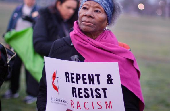 A woman holds a sign during an April 4, 2018, peace and unity rally. The rally followed the Commission on Religion and Race's participation in the United to End Racism Prayer Walk in Washington. Photo courtesy of the Commission on Religion and Race.