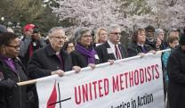 Bishops (from left) LaTrelle Easterling, Bruce R. Ough, Hope Morgan Ward, Bob Farr and Karen Oliveto carry a United Methodist banner. Photo by Kathy L. Gilbert, UMNS