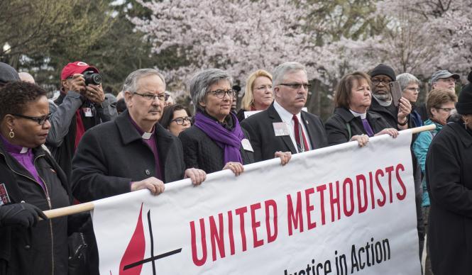 Bishops (from left) LaTrelle Easterling, Bruce R. Ough, Hope Morgan Ward, Bob Farr and Karen Oliveto carry a United Methodist banner. Photo by Kathy L. Gilbert, UMNS