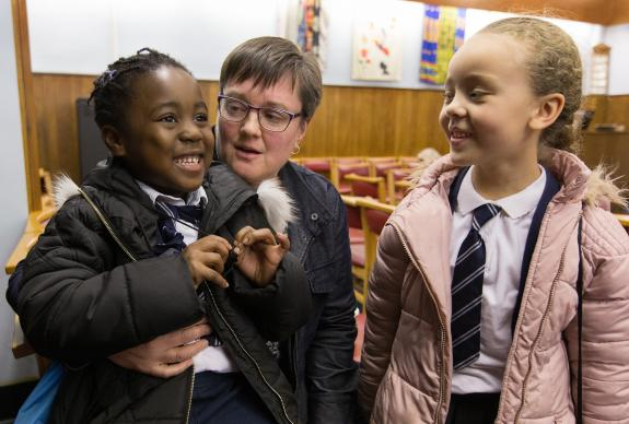 Nwarebea Baffoe (left) and Rebecca Henry, both age 6, stop by after school to visit with the Rev. Janet Corlett at Bermondsey Central Hall Methodist Church in London.  Photo by Mike DuBose.