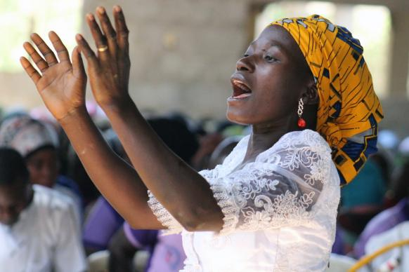 Evelyn Lot directs the Women Fellowship Choir during worship at Abuja Area 1 United Methodist Church in Abjua, Nigeria, March 4, 2018. The church is facing the threat of a federal government penalty for failing to meet construction deadlines due to a lack of funds to complete the structure. Photo by E Julu Swen, UMNS.
