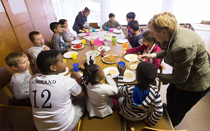 Volunteer Hannah Guzinski helps serve a meal to immigrant children in an art education  enrichment program at the United Methodist Peace Church in Hamburg, Germany. A number of United Methodist congregations in Germany are assisting refugees. Photo by Mike DuBose, UMNS.