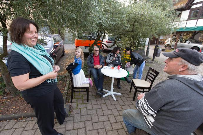 The Rev. Heike Miller (left) visits with Harry Faust (right) and other community members outside the United Methodist Church in Lorsbach during Café Gegenüber, a weekly gathering for coffee, cake and coversation. The café helps the church serve as a social center in the community. Photo by Mike DuBose, UMNS.