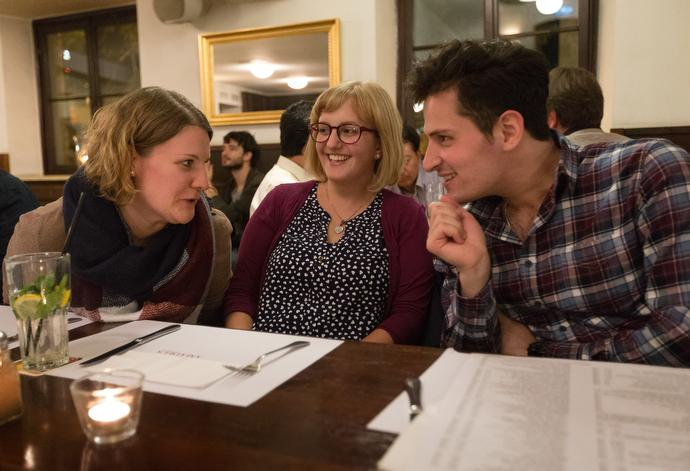 """The Rev. Mareike Bloedt (center), pastor of the United Methodist Church in Central Stuttgart, Germany, visits with Miriam Schäuble (left) and Iskandar Obaid during a monthly dinner gathering at a local restaurant. """"I saw there was nothing for young adults. They were losing their connection with church,"""" Bloedt said. """"We have five or six people every month, sometimes as many as 15. We talk a lot about faith."""" Photo by Mike DuBose."""