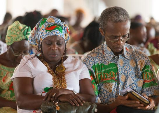 Parishioners pray during worship at Canaan United Methodist Church in Abidjan, Côte d'Ivoire. Church leaders have been working to determine which parts of The United Methodist Church's policy book must apply throughout the multinational denomination and what parts can be adapted for use in Africa, Europe and Asia. Photo by Mike DuBose, UMNS.
