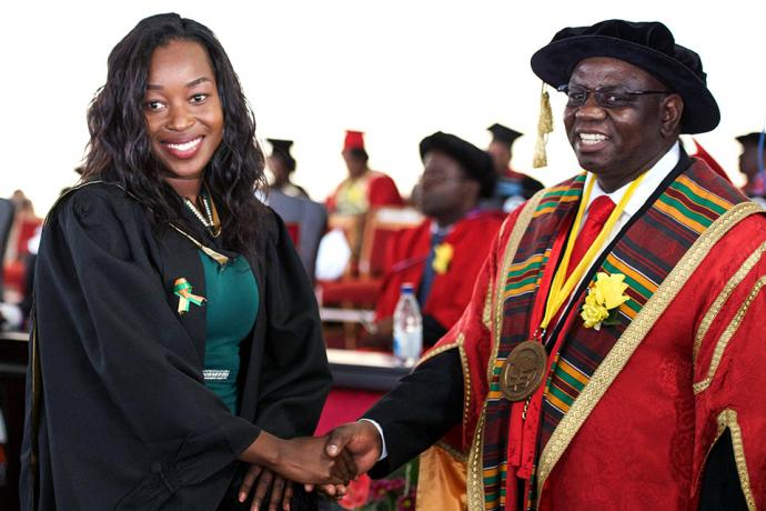 Gracious Matika shakes hands with Africa University Vice Chancellor Munashe Furusa M. Furusa after she graduated on June 9. Photo courtesy of Information and Public Affairs Office, Africa University.