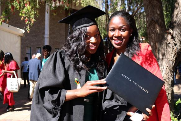 Gracious Matika (left) and her sister, Varaidzo, pose with her new diploma after Africa University's June 9 graduation ceremony. Photo by Eveline Chikwanah, UMNS.