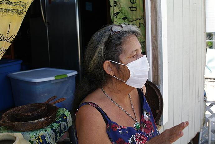 Donna Allison, a resident of Big Pine Key, Fla., has to wear a mask when she leaves her trailer, due to mold growing in the abandoned home next to hers. Photo by Gustavo Vasquez, UMNS.