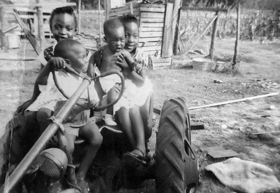 James H. Salley sits in the driver seat of a tractor as a child in 1957 surrounded by three of his sisters. Salley, who grew up on his family's farm in Allendale County, S.C., has established a scholarship at Africa University in honor of his hardworking parents, Marie and James Salley. Photo courtesy of James H. Salley.
