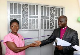 Sierra Leone Bishop John K. Yambasu (right) hands over keys to the new health center to the nurse-in-charge. The government, through the Moyamba District Health Management Team, will manage the center. Photo by Phileas Jusu, UMNS.