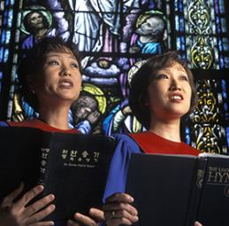 Two women sing from the Korean hymnal. Photo by Mike DuBose, UMNS.