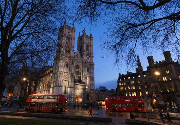 Double-decker buses drive past Westminster Abbey in London, across the street from Methodist Central Hall, Westminster. Photo by Mike DuBose, UMNS.