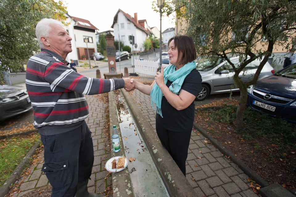 The Rev. Heike Miller (right) visits with Dieter Kugelmann outside the United Methodist Church in Lorsbach, Germany, during Café Gegenüber, a weekly gathering for coffee, cake and conversation. Photo by Mike DuBose, UMNS.
