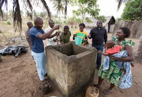 The Rev. Jean Claude Masuka Maleka (wearing clerical collar) visits with villagers at the community well in Niangoussou, Côte d'Ivoire. Lowering a bucket into the well is Djibi Dre N'Brien Moïse. Maleka, a United Methodist missionary, leads efforts to drill wells in remote Ivoirian villages. Photo by Mike DuBose, UMNS.