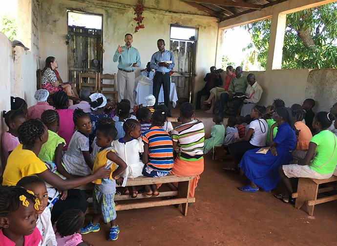 "The Rev. Matt Henson (standing, left, in green shirt) speaks in a church in Sobier, Haiti. Henson, president of National Association of United Methodist Evangelists, hopes to increase awareness of the association and in turn help the church connect new people with the ""old, old story."" Photo courtesy of The Rev. Matt Henson."